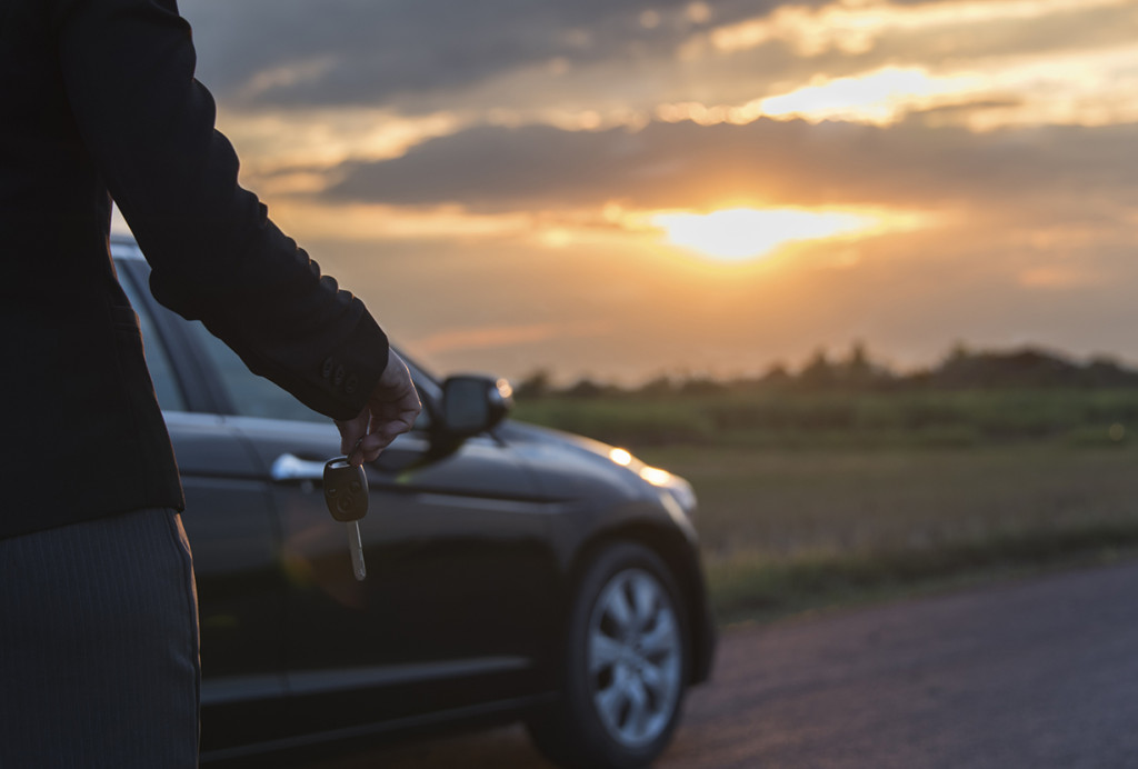 Person standing with car key next to car.