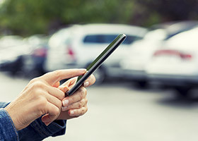 Woman uses her cell phone application connected to her car.
