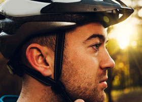 A man wearing a bicycle helmet. Wearing bicycle helmets has been found to reduce head injury by 48%.